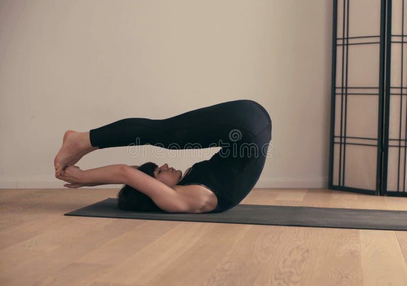 Una giovane donna che esegue yoga-asanas nel corridoio immagini stock