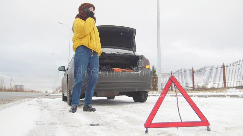 Una giovane donna che fa una pausa un'automobile rotta Chiamate sul telefono per un aiuto fotografia stock