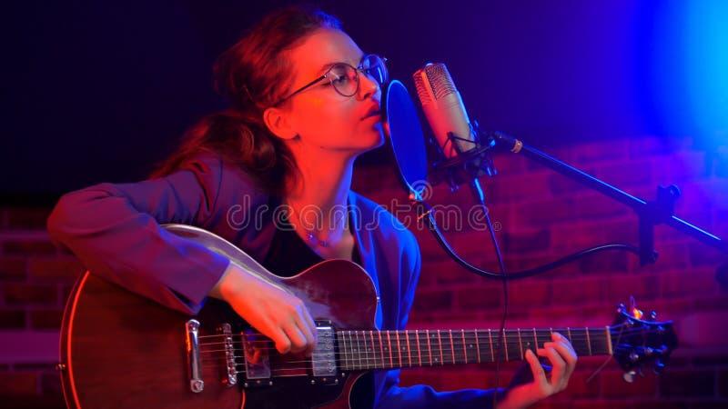 Una giovane donna che gioca chitarra e che canta nell'illuminazione al neon fotografia stock libera da diritti