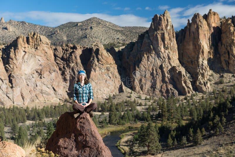 Una giovane donna che medita nelle montagne immagini stock