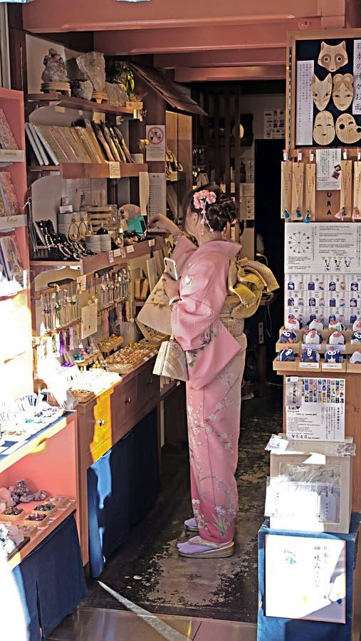 Una giovane donna che porta un kimono splendido in un deposito a Kyoto, Giappone immagini stock libere da diritti