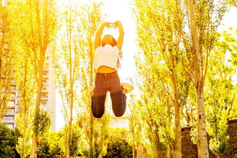 Una giovane donna che salta in un parco un giorno soleggiato immagine stock libera da diritti