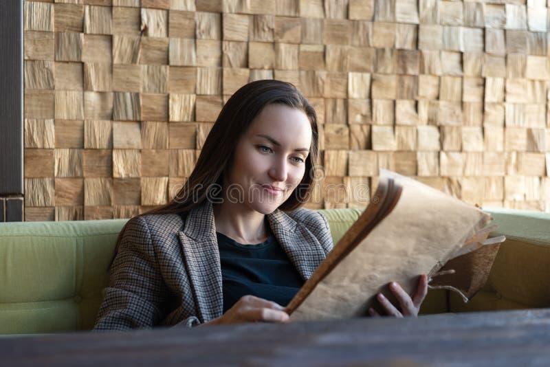 Una giovane donna che si siede in un ristorante con un menu in sue mani opera una scelta dei piatti immagine stock libera da diritti