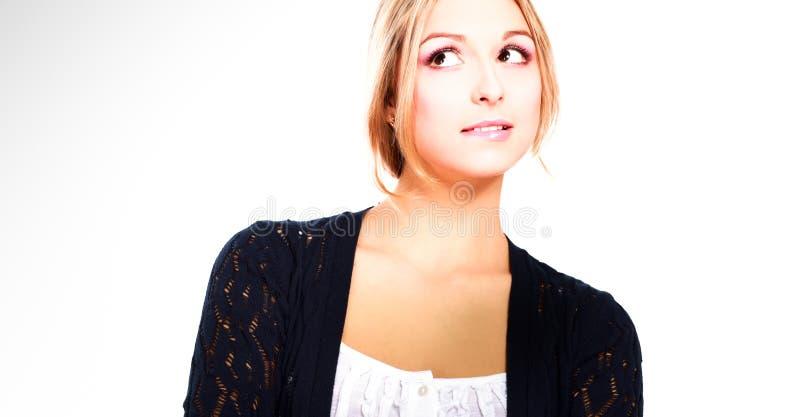 Una giovane donna che sta sul fondo bianco immagine stock