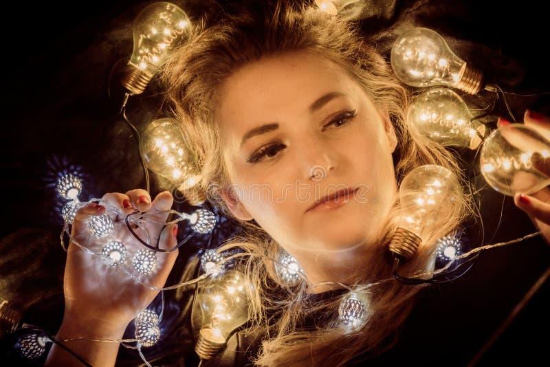 Una giovane donna circondata dalle luci fotografia stock