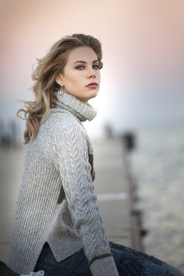 Una giovane donna con capelli biondi lunghi che si siedono su un pilastro al tramonto immagini stock