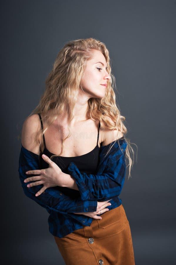 Una giovane donna con capelli ondulati biondi lunghi sta ballando contro un fondo scuro Emozioni positive, felici, stile dei pant immagini stock