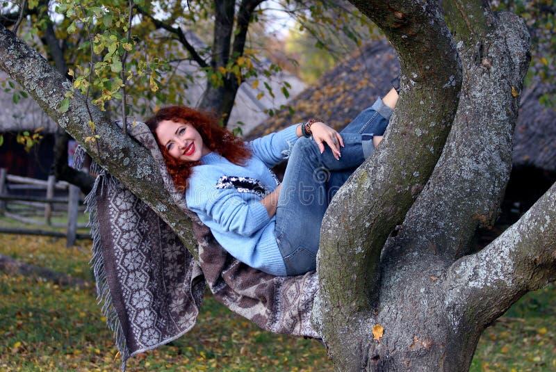 Una giovane donna con capelli rossi e un bello sorriso sta trovandosi su una coperta che è spanta su un albero I sorrisi e esamin fotografie stock