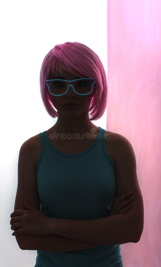 Una giovane donna con i capelli rosa ed i vetri del neon fotografie stock libere da diritti