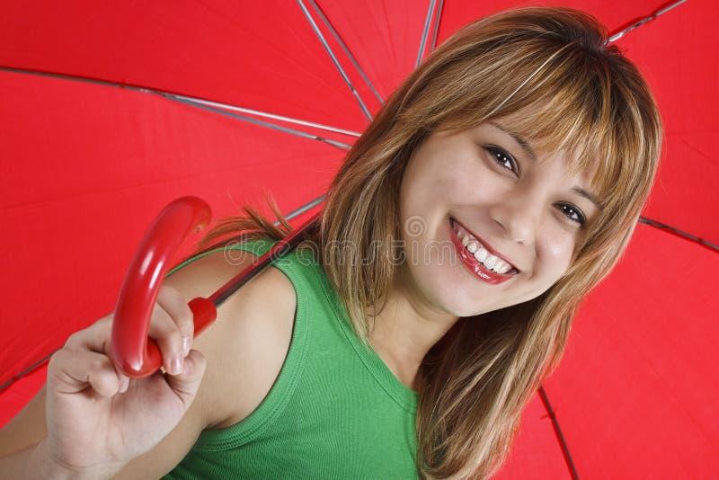 Una giovane donna con un ombrello rosso immagini stock