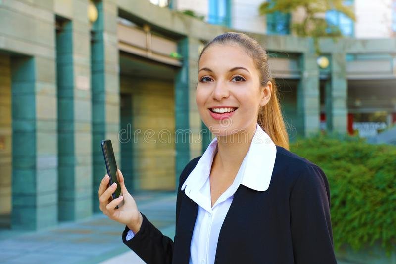 Una giovane donna d'affari di successo che usa il cellulare all'esterno Bella giovane donna in tuta d'ufficio con smartphone e fotografia stock
