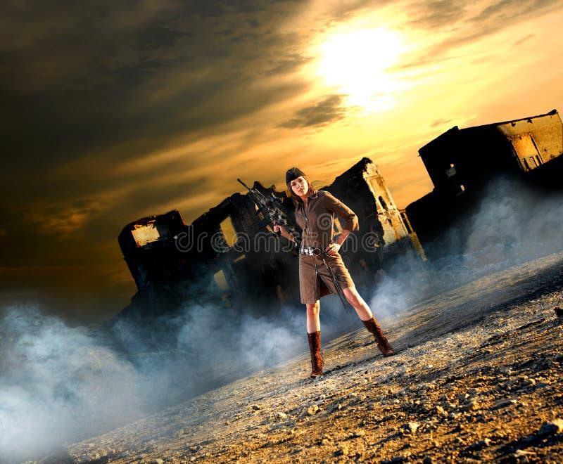 Una giovane donna del brunette che tiene un fucile del tiratore franco fotografia stock libera da diritti