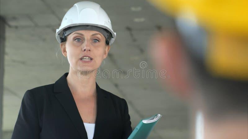 Una giovane donna dell'architetto che lavora al cantiere, parlante con il suo collega fotografia stock libera da diritti