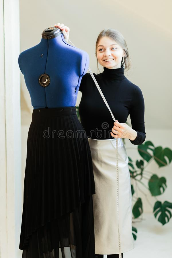 Una giovane donna della cucitrice mette i vestiti sul manichino fotografie stock