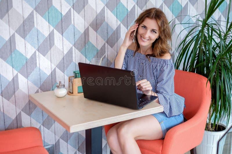 Una giovane donna di affari attraente che per mezzo del suoi telefono e computer portatile ad un caffè immagine stock