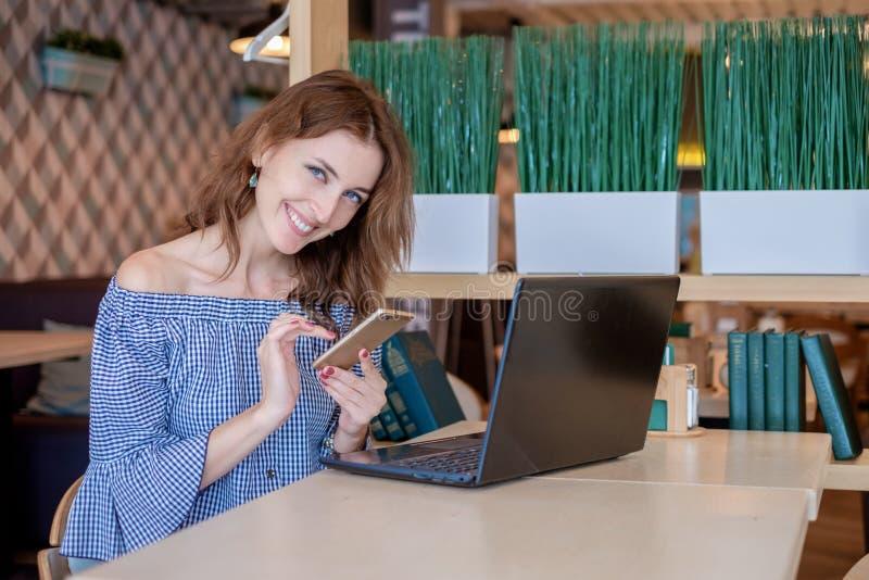Una giovane donna di affari attraente che per mezzo del suoi telefono e computer portatile ad un caffè fotografia stock