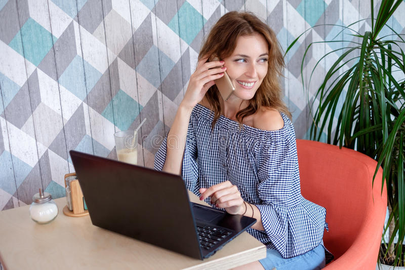 Una giovane donna di affari attraente che per mezzo del suoi telefono e computer portatile ad un caffè fotografia stock libera da diritti