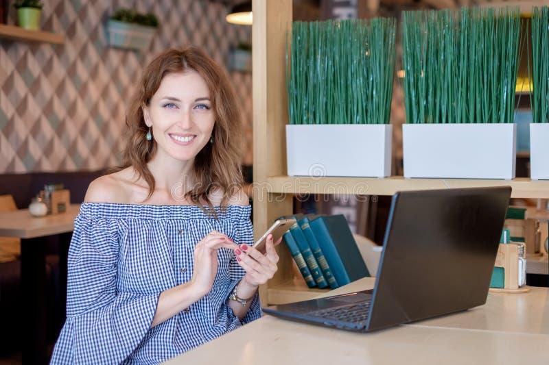 Una giovane donna di affari attraente che per mezzo del suoi telefono e computer portatile ad un caffè fotografie stock