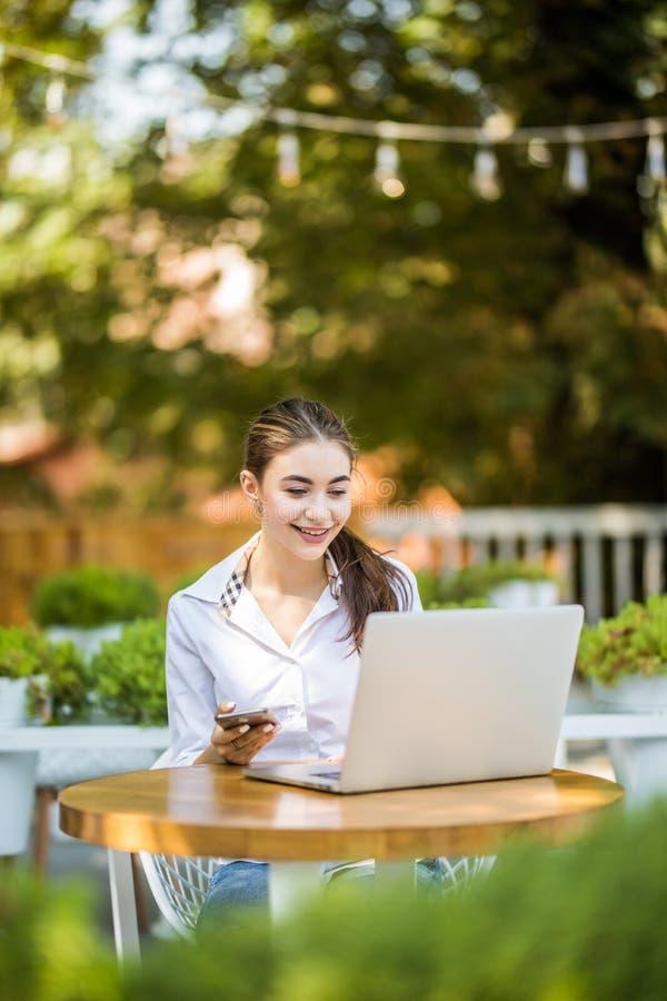 Una giovane donna di affari attraente che per mezzo del suoi telefono e computer portatile ad un caffè all'aperto fotografie stock