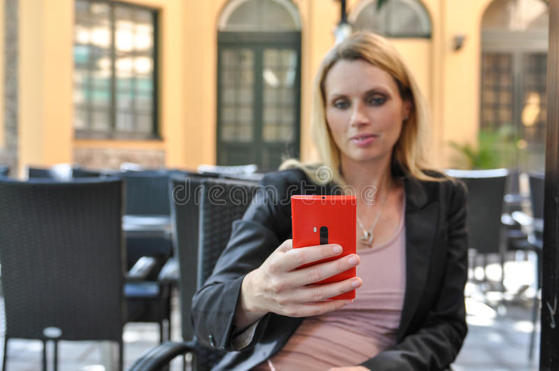 Una Giovane Donna Di Affari Che Per Mezzo Di Uno Smart Phone All Aperto Fotografia Stock