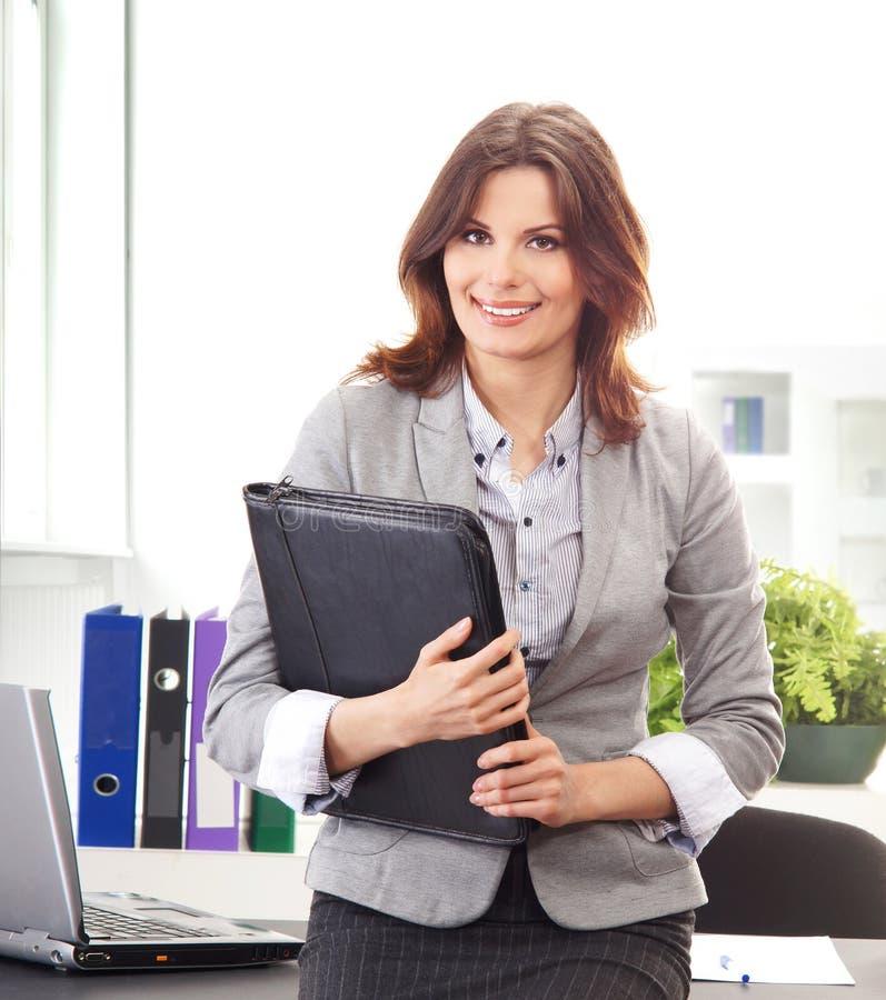 Una giovane donna di affari del brunette che tiene un dispositivo di piegatura immagine stock