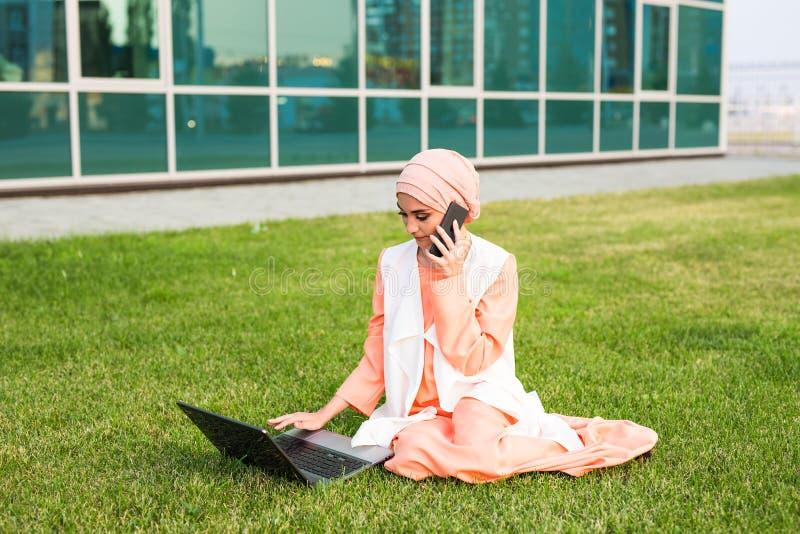 Una giovane donna di affari musulmana graziosa in un parco mentre parlando sullo smartphone che esamina il computer portatile fotografia stock