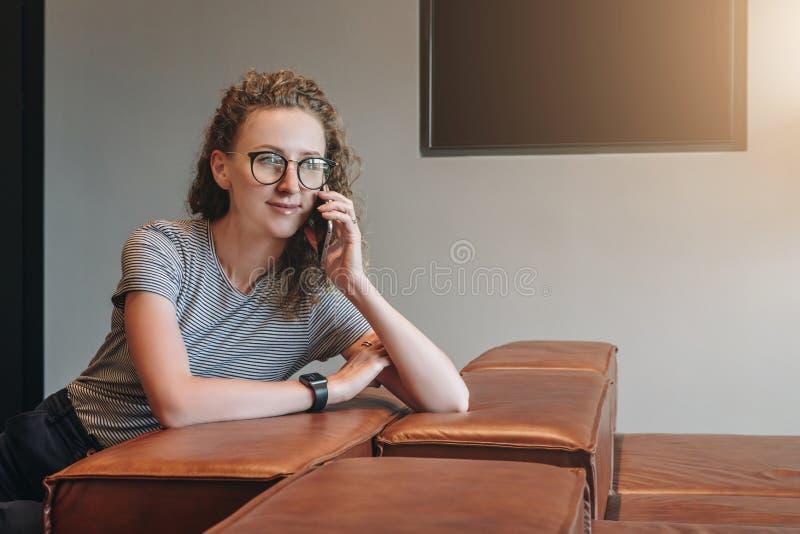 Una giovane donna di affari in vetri sta sedendosi sul sofà di cuoio nell'ingresso dell'hotel, la sala di attesa, caffè e sta par immagine stock
