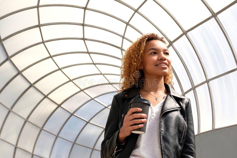 Una giovane donna di colore su una passeggiata in un ambiente urbano Una bella ragazza afroamericana moderna dello studente in un immagini stock