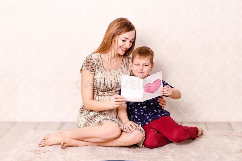 Una giovane donna e un bambino con una cartolina in vostre mani fotografie stock