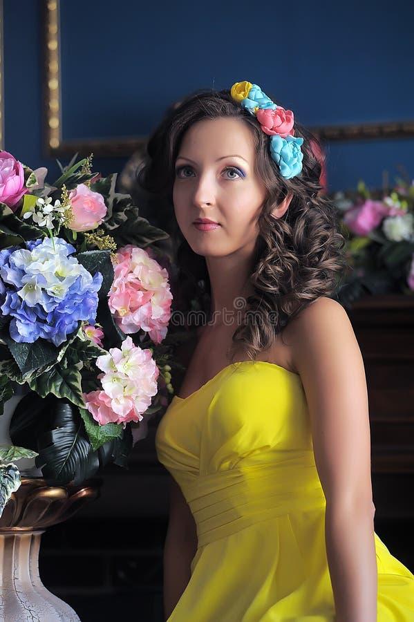 Una giovane donna elegante in un vestito giallo fotografie stock