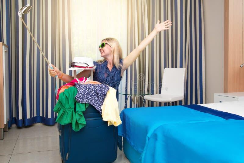 Una giovane donna esamina una valigia sulla vacanza Campeggiatore felice di Selfie fotografia stock libera da diritti