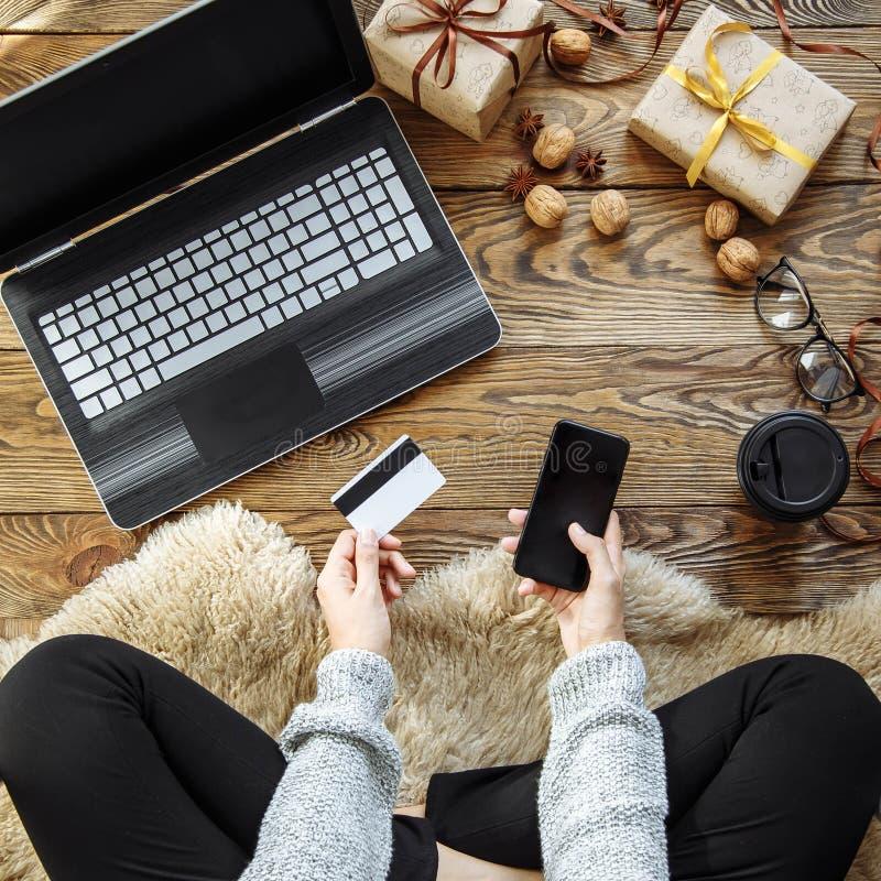 Una giovane donna fa gli acquisti con uno smartphone e una carta di credito Acquisto in linea Regali di natale immagine stock libera da diritti