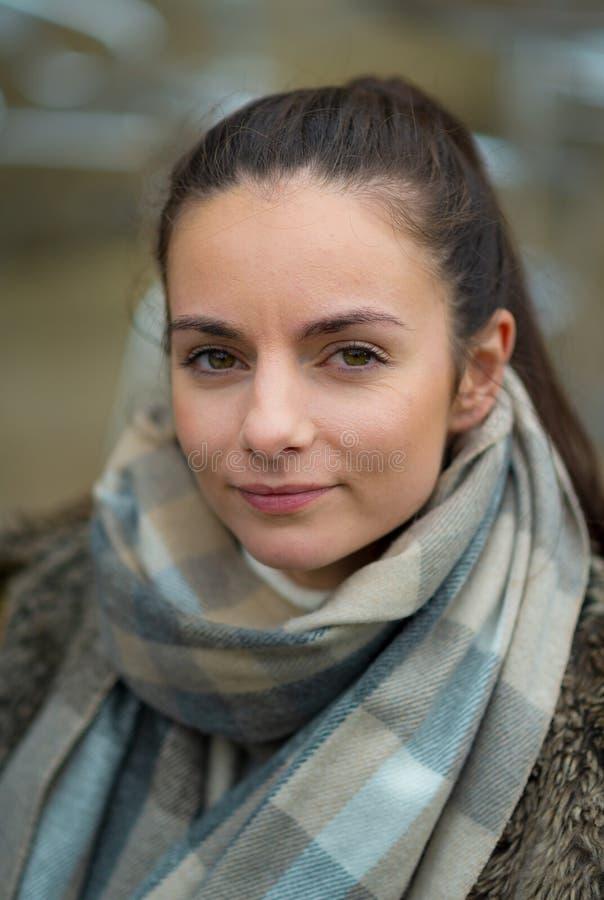 Una giovane donna femminile bianca esamina la macchina fotografica vestita per l'inverno fotografia stock libera da diritti