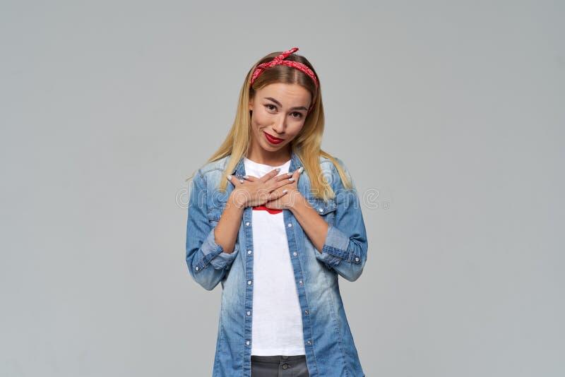 Una giovane donna graziosa in una camicia del denim piega morbidamente le sue mani sul suo petto e sorride confuso fotografie stock