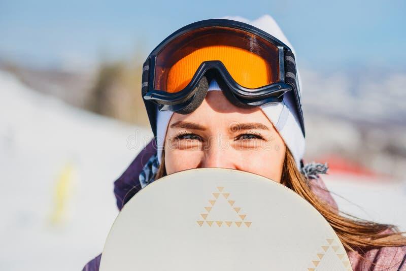 Una giovane donna guarda dallo snowboard fotografie stock