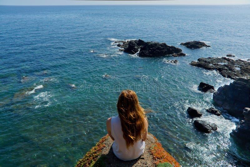 Una giovane donna guarda fuori sopra il mare dalle lucertole indica in Cornovaglia, Regno Unito fotografia stock libera da diritti