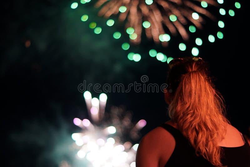 Una giovane donna guarda i fuochi d'artificio immagine stock libera da diritti