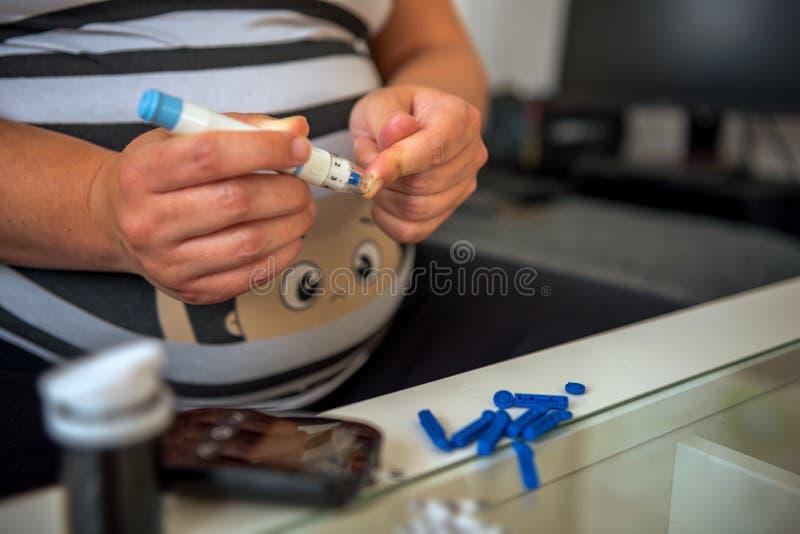 Una giovane donna incinta vuole misurare la sua glicemia fotografie stock