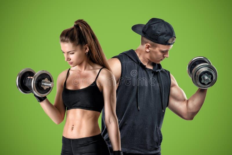 Una giovane donna muscolare e un supporto adatto dell'uomo su un fondo verde immagine stock libera da diritti