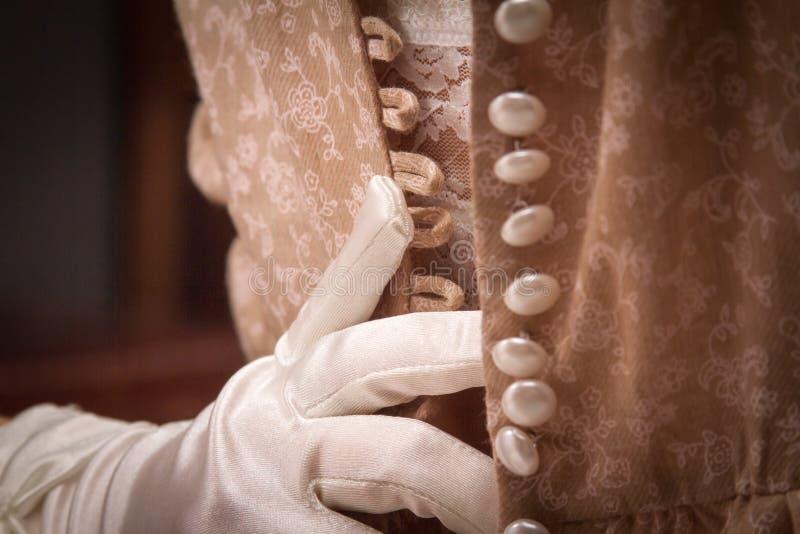 Una giovane donna nella biancheria d'annata ed in guanti bianchi aprire la zip il vestito della sua amica, molti bottoni Ha aggiu fotografia stock libera da diritti
