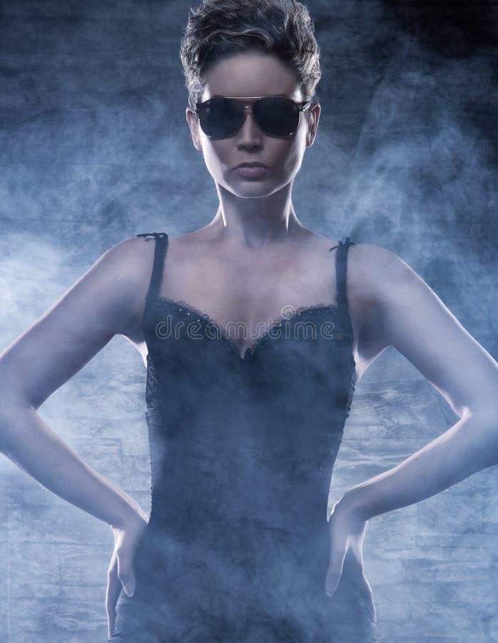 Una giovane donna in occhiali da sole e vestiti erotici fotografie stock