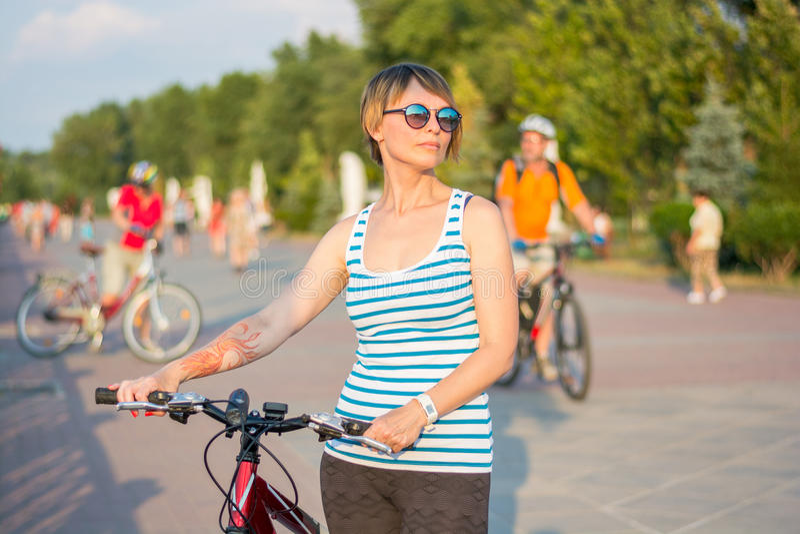 Una giovane donna in occhiali da sole sta con una bicicletta sul promena fotografia stock