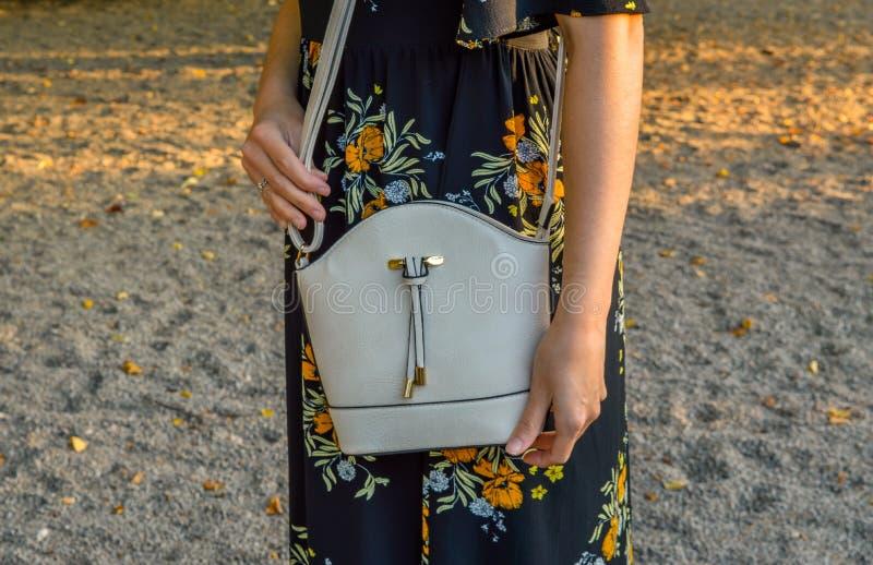 Una giovane donna, portando un vestito floreale, tenente una mini borsa fotografia stock