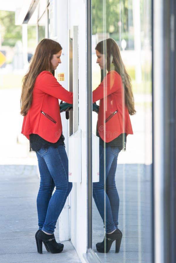 Una giovane donna prende i soldi da un BANCOMAT fotografia stock libera da diritti