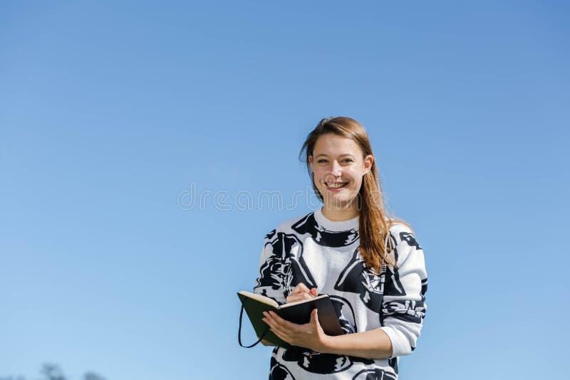 Una giovane donna prende le note fotografie stock