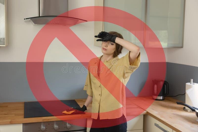 Una giovane donna pulisce nella cucina, lavante i piatti fotografia stock