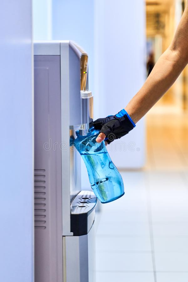 Una giovane donna raccoglie l'acqua dal dispositivo di raffreddamento in bottiglia per estiguere la sua sete dopo l'allenamento i fotografia stock