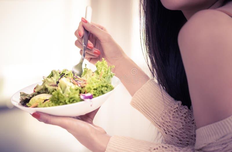 Una giovane donna sana mangia insalata verde per uno stile di vita sano e insalata fotografia stock