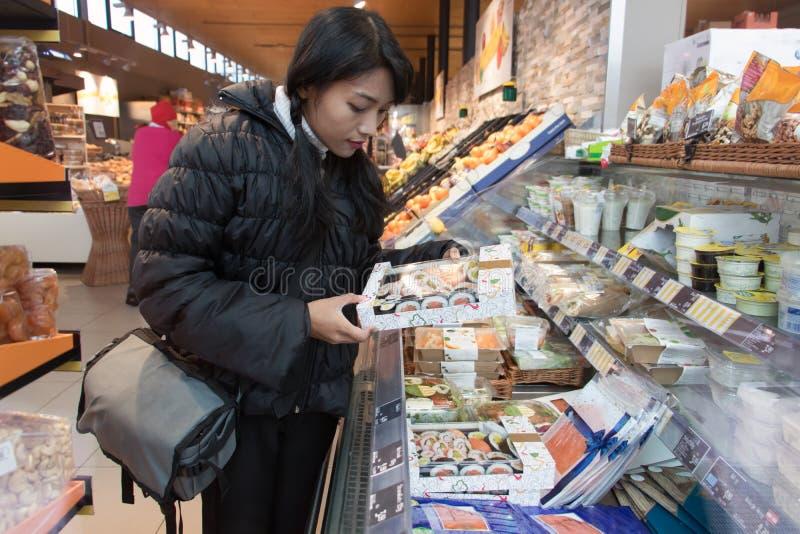 Una giovane donna sceglie l'alimento in un negozio fotografia stock