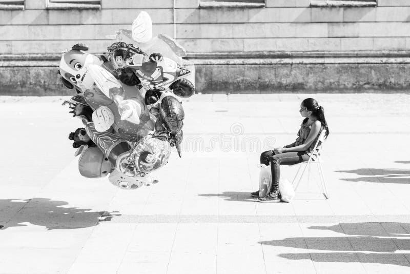 Una giovane donna, sedentesi in una sedia, vende i palloni fotografia stock libera da diritti
